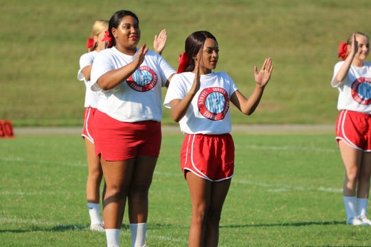 Nina Martin (left) and Bianca Hughes (right) cheer on the field for the Meet the Braves event on Friday evening.
