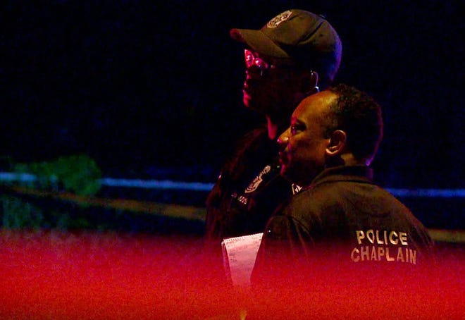 An IMPD officer and a chaplain observe the shooting scene at the 2600 block of Ethel Avenue on Sunday.