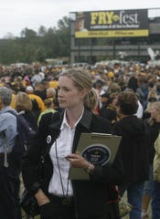 "Guinness World Records judge Amanda Mochan watches as Iowa fans arrive to participate in the Guinness World Record for the most people simultaneously doing the ""Hokey Pokey"" during FryFest, Friday, Sept. 9, 2010, in Coralville, Iowa."