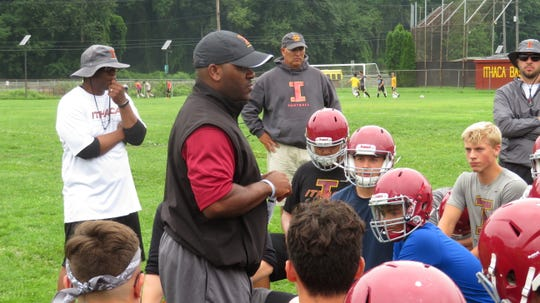 Coach Clarence Welch coaches Little Red football players as they take a knee.