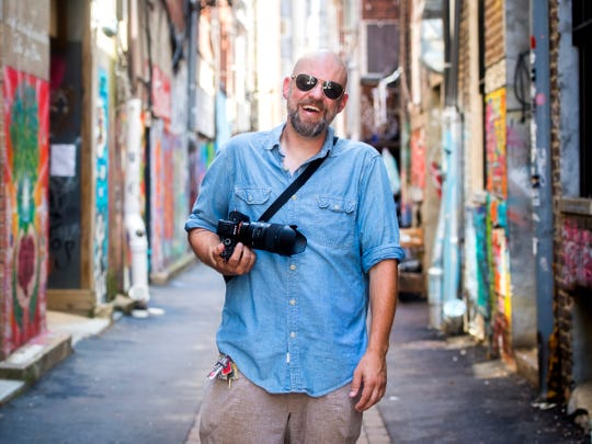 Tod Sheley, a visually impaired photographer, poses in Strong Alley. During First Friday on Sept. 7, the alley will host a live art competition, while Sheley's photographs will be on display at Downtown Grill & Brewery.