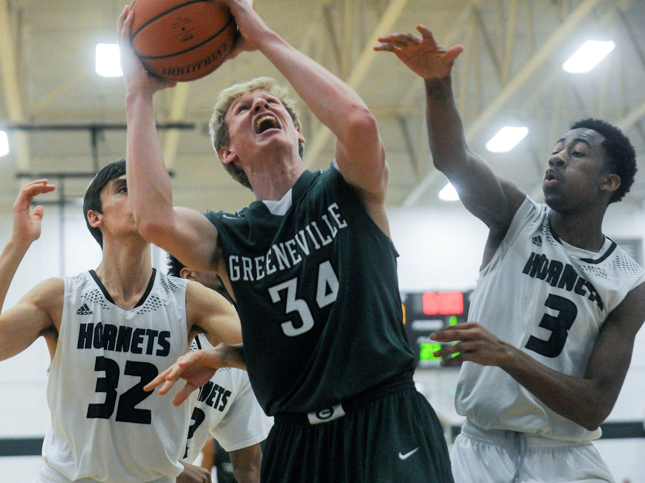 Carter's Austin Hayes and Jordan Bowden (3) try to block Greeneville's Thomas Burkey (34) as he goes up for a shot  during the Class AA state sectional game where Carter defeated Greeneville  85-71 at Carter high school Tuesday, Mar. 3, 2015.