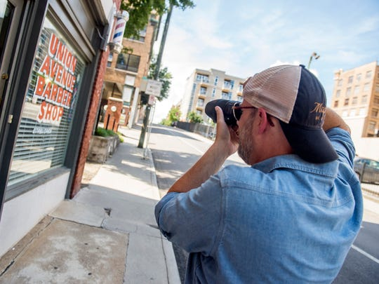 Tod Sheley takes photographs in downtown Knoxville on Friday, Aug. 10, 2018.