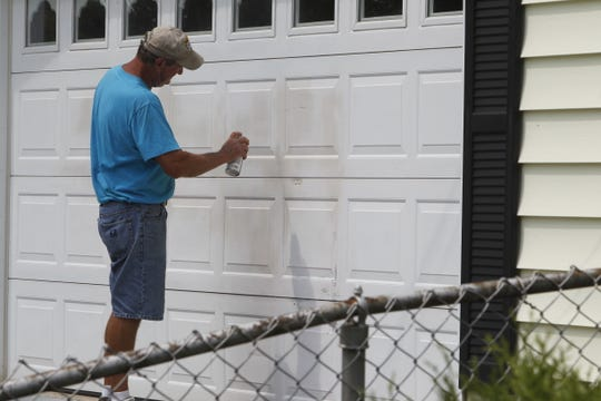 Dave Shoaf spent part of his Monday afternoon spray painting over graffiti left on his mother's garage door. Police took more than 20 reports of vandalism Saturday  to cars, fences, garage in the Edgelea. They took even more reports on Monday.