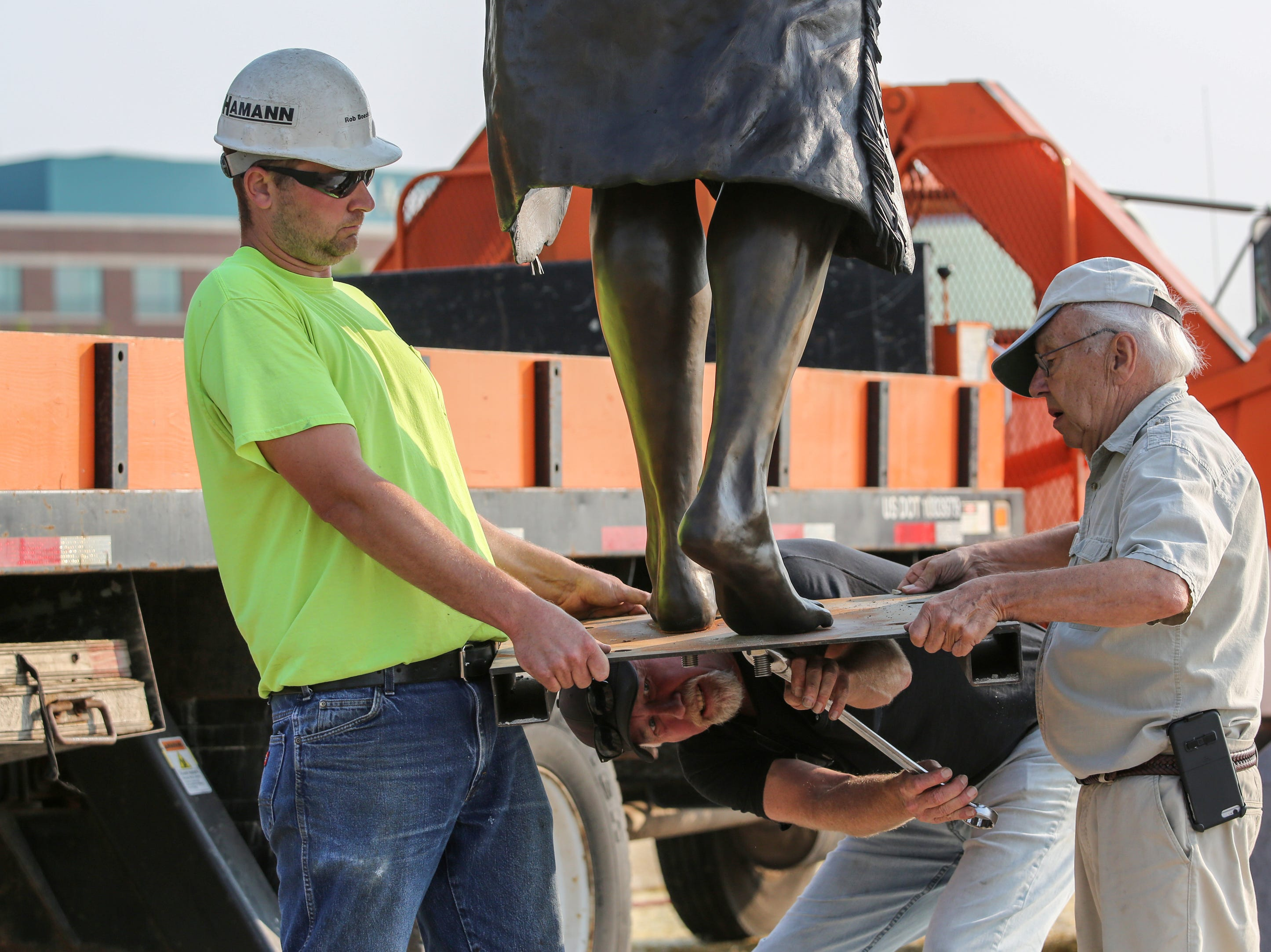 "Foundry owner Steve Parks, of Joseph, Ore., removes the base from a piece of the Spirit of the Rivers sculpture as crane operator Rob Boeckman and artist R.T. ""Skip"" Wallen hold it steady during the installation Monday, August 13, 2018, in Two Rivers, Wis. Josh Clark/USA TODAY NETWORK-Wisconsin"