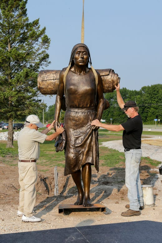 """Artist R.T. """"Skip"""" Wallen, left, and sculpture installation expert Steve Parks hold steady the first piece of the Spirit of the Rivers sculpture before its installation Monday, August 13, 2018, in Two Rivers, Wis. Josh Clark/USA TODAY NETWORK-Wisconsin"""