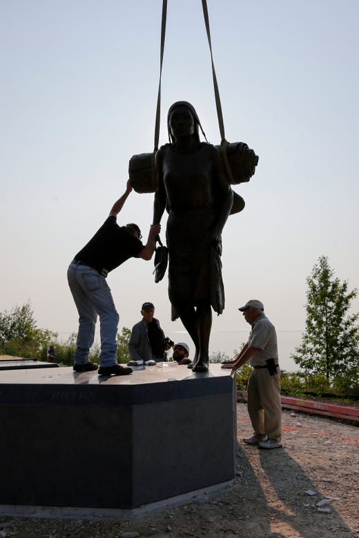 """A crew led by the artist R.T. """"Skip"""" Wallen, right, and foundry owner Steve Parks, left, sets the first piece of the Spirit of the Rivers sculpture on the granite base next to Lake Michigan Monday, August 13, 2018, in Two Rivers, Wis. Josh Clark/USA TODAY NETWORK-Wisconsin"""
