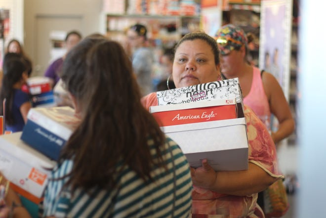Maria Covarrubias waits in line at Payless ShoeSource with boxes of shoes Monday. The local nonprofit Cents for Shoes was giving away vouchers for free or reduced-price shoes to eligible families. Eligible children and their parents will be able to receive vouchers at Payless again from 4 to 8 p.m. Wednesday, Aug. 15.