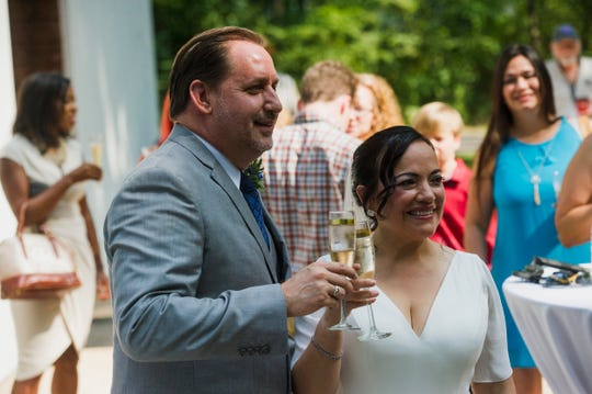 August 13, 2018 - Newlywed couple Marc Caudel, left, and Julie Guardado raise glasses for a toast after their ceremony at the new Chapel in the Woods adjacent to The Guest House at Graceland. Theirs was the first ceremony in the new chapel.