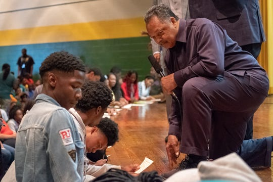 Rev. Jesse Jackson answers a student's question about a voting application form at Booker T. Washington High School on Monday.
