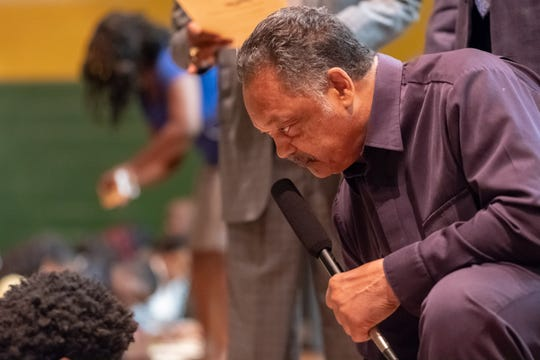 Rev. Jesse Jackson kneels to interact with students as they fill out voter registration forms after his talk to an assembly at Booker T. Washington High School on Monday.