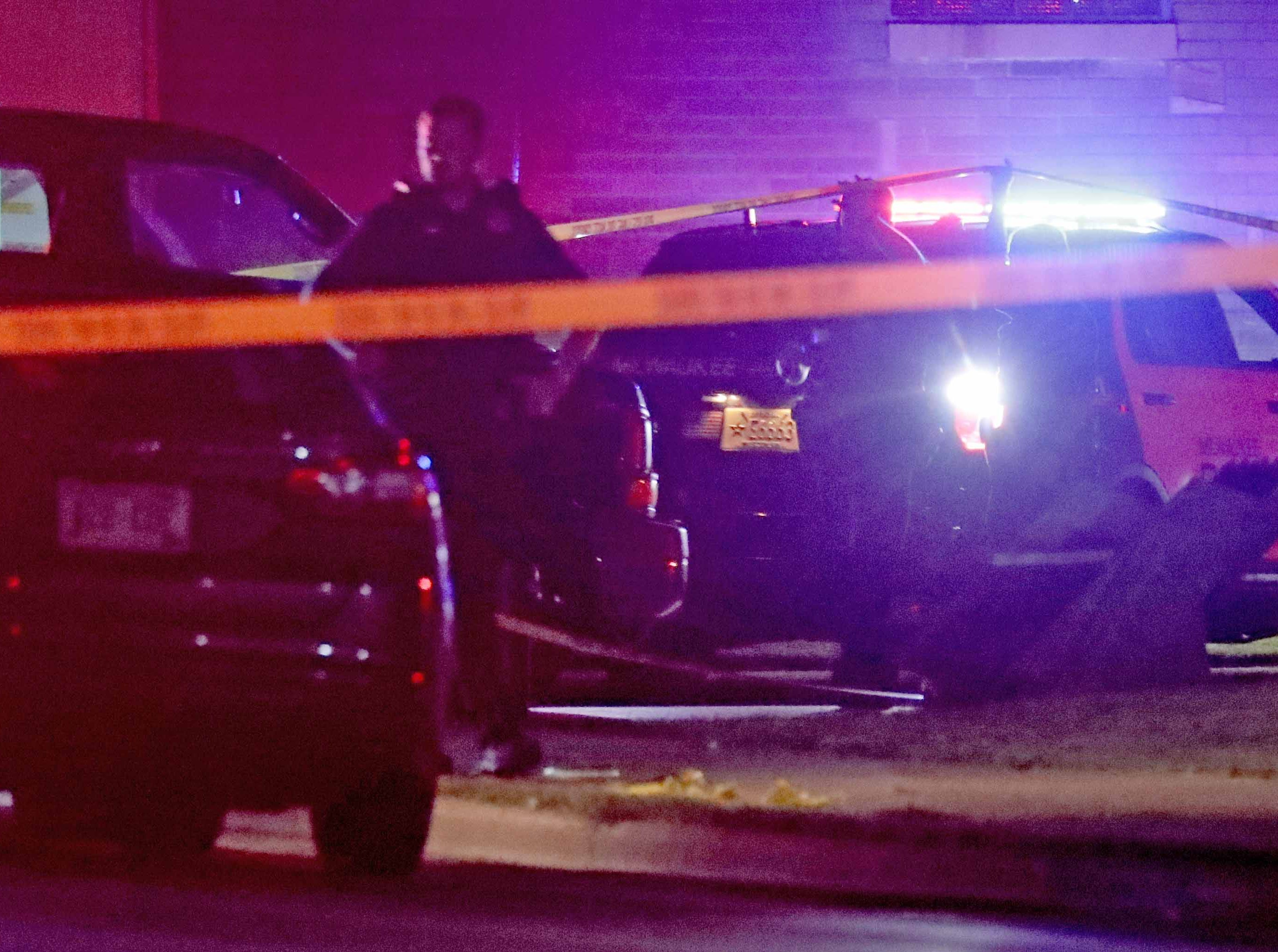 Police investigate the scene of a fatal shooting at the intersection of North 10th and West Burleigh streets in Milwaukee on Sunday. According to the Milwaukee Police Department, a man was shot to death and two boys, ages 4 and 14, were wounded.