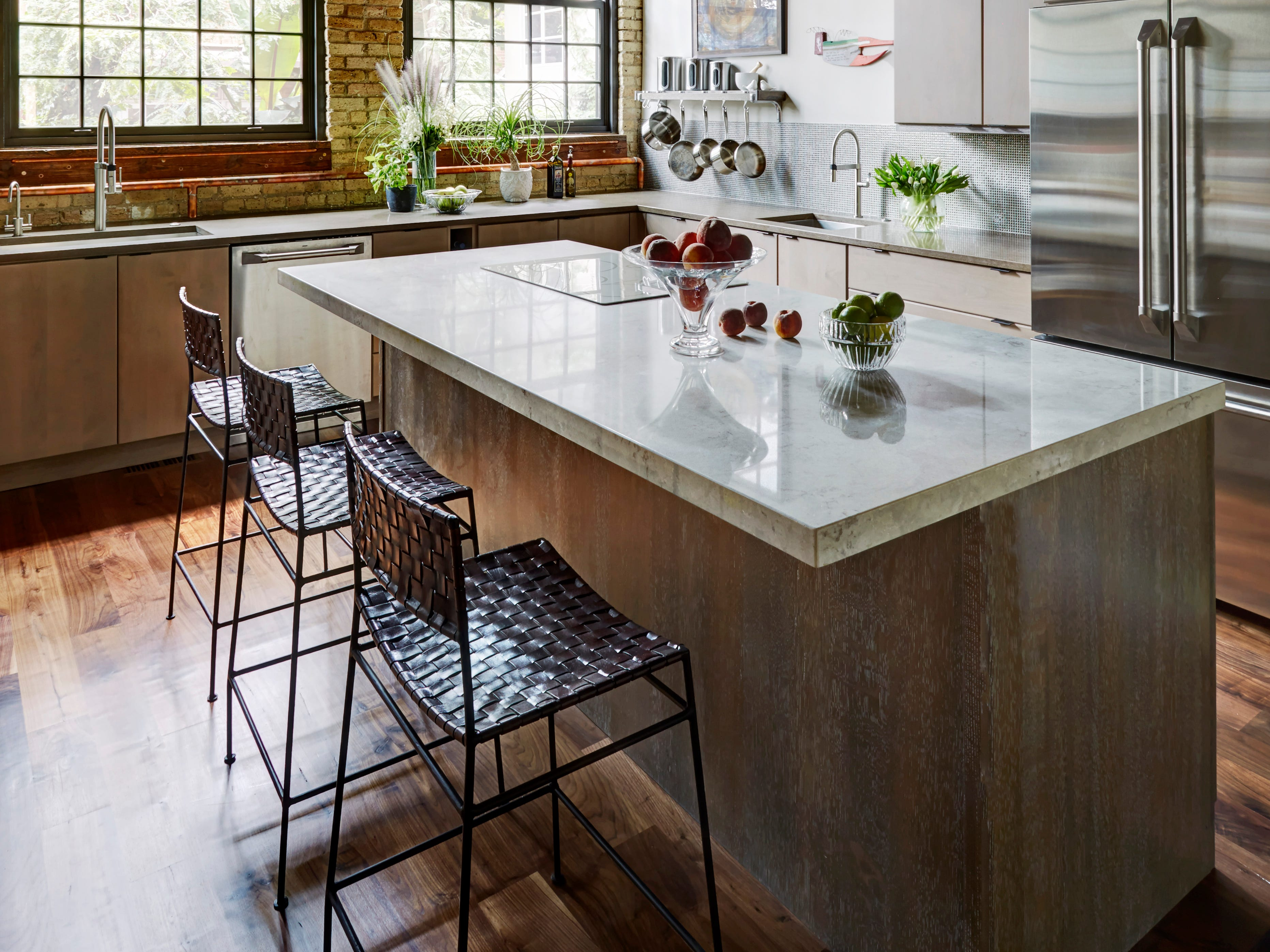 When a former Chicago banjo factory was renovated a large island was added. It was topped with Caesarstone quartz and is now the centerpiece of the kitchen. (FMA Interior Design)