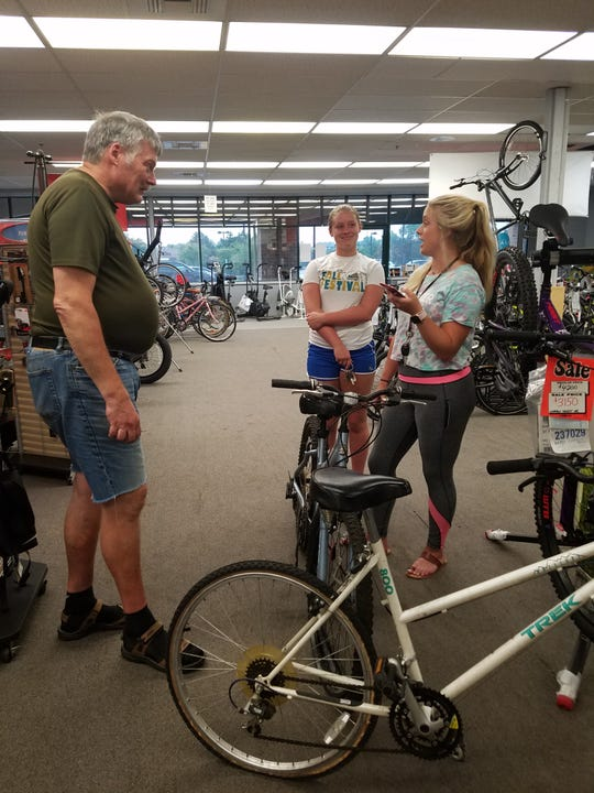 Brookfield Cycle and Fitness employee Pete Schrubbe discusses a repair with Demi Crow and Haley Crow of Brookfield on Aug. 9.