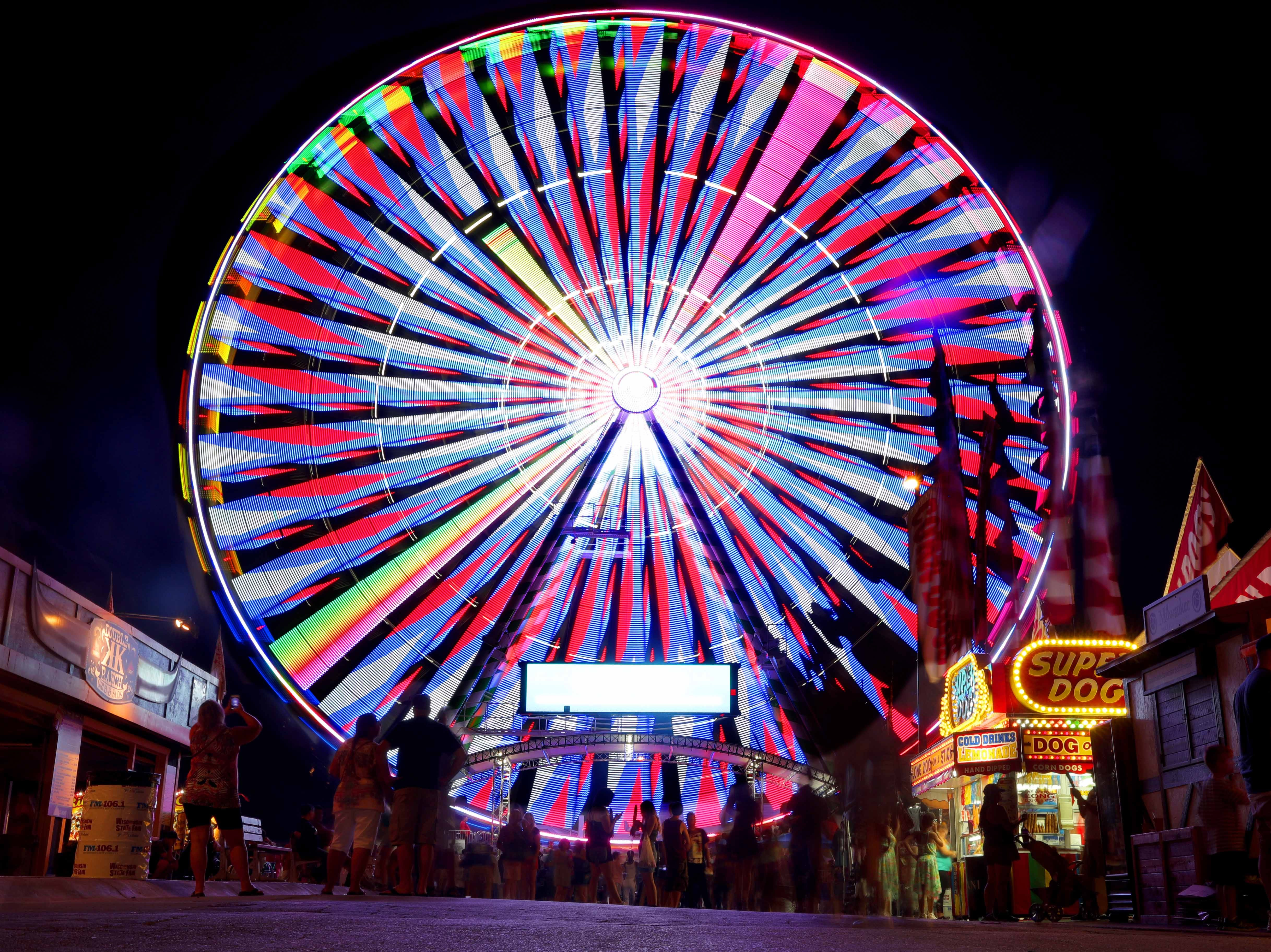 The WonderFair Wheel, which stands 15 stories tall, glows on the final night of the Wisconsin State Fair Sunday, Aug. 12, 2018.
