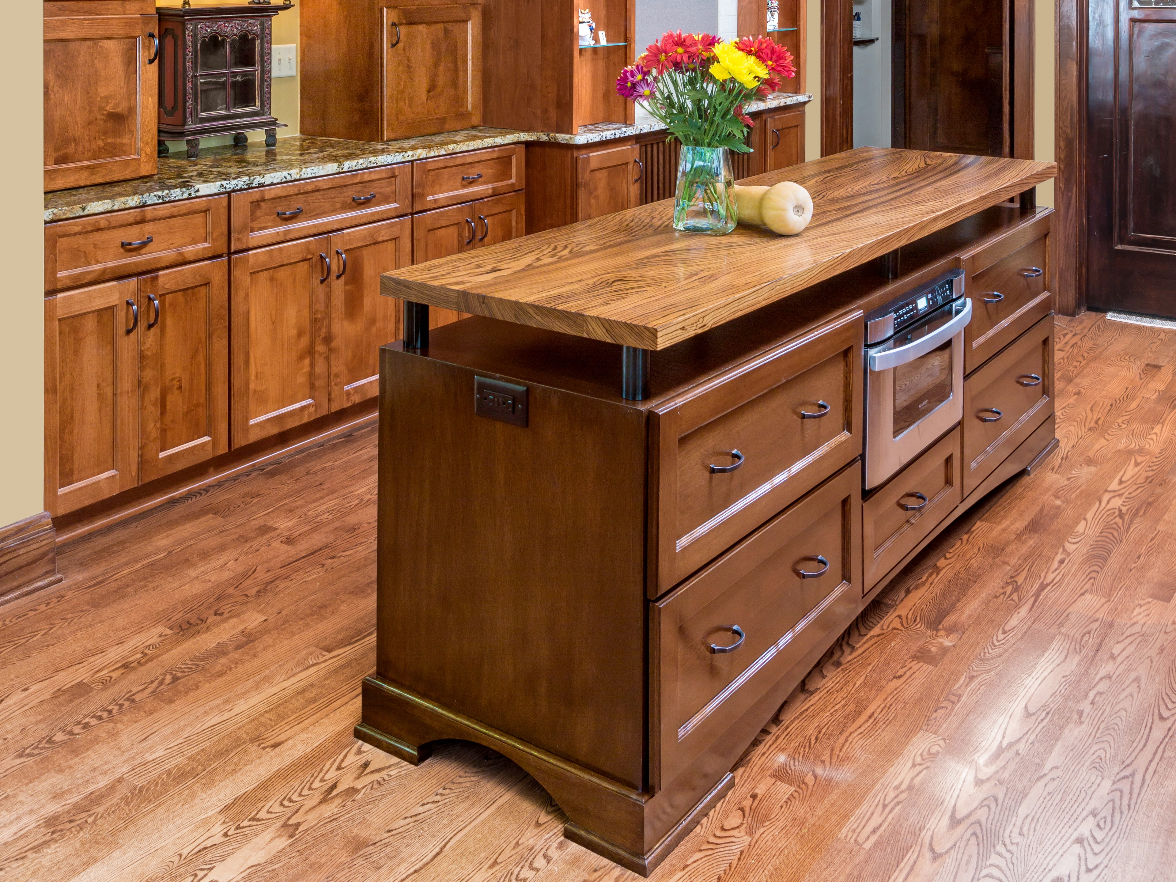 With a floating Zebrawood countertop, large drawers, and furniture style base, this island takes on the look of a custom piece of furniture.