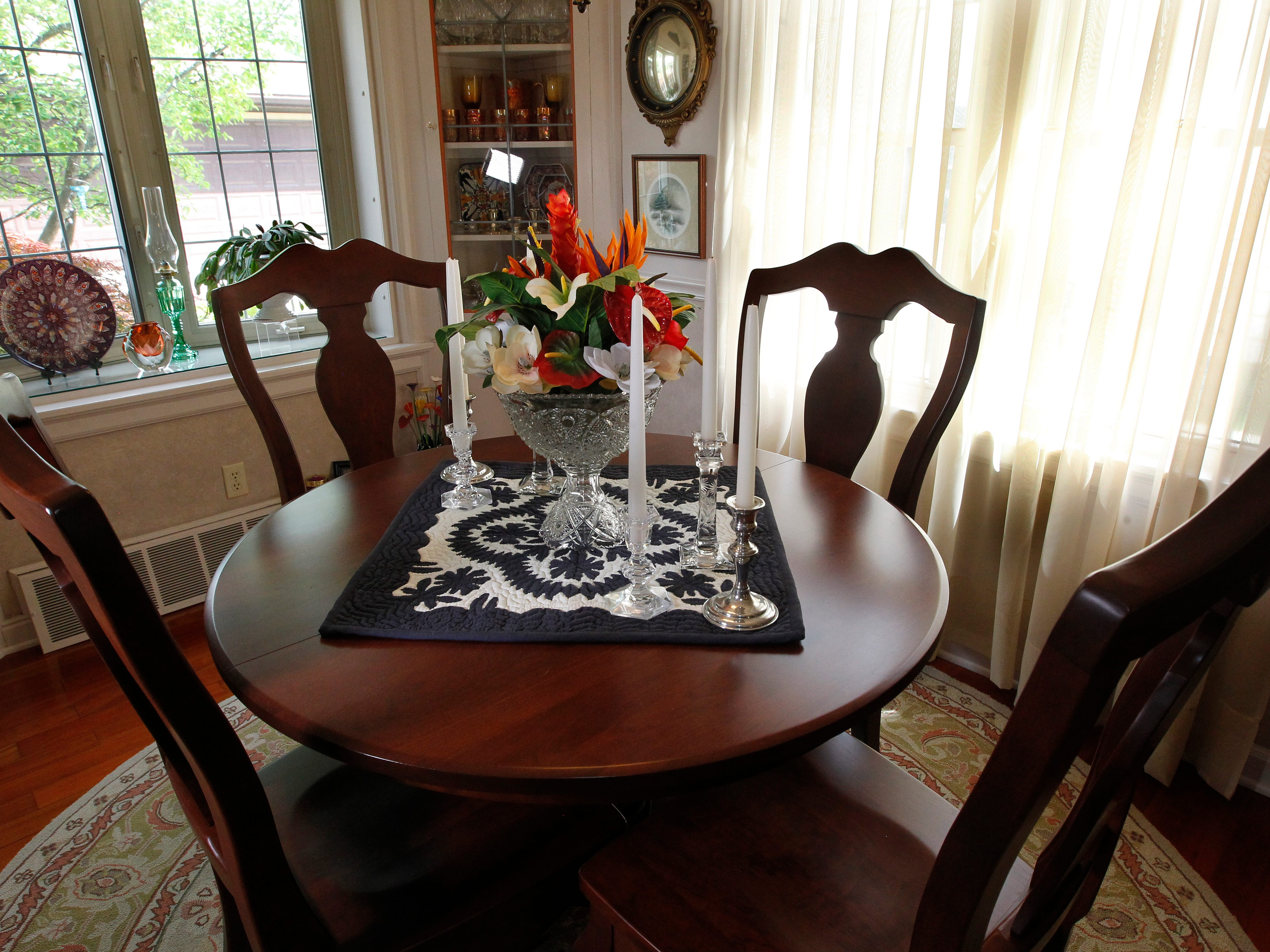 The dining room features this Amish table and chairs, built-in cabinets and multiple windows.