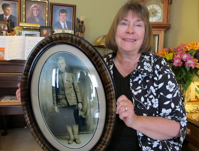 Laurie DeMoss holds a photo of her grandfather Grant Hill in his World War I Army uniform. Hill was severely wounded in the Battle of Hamel in France on July 4, 1918, and 100 years later DeMoss and her family traveled to the small French town where the battle occurred for commemoration ceremonies.