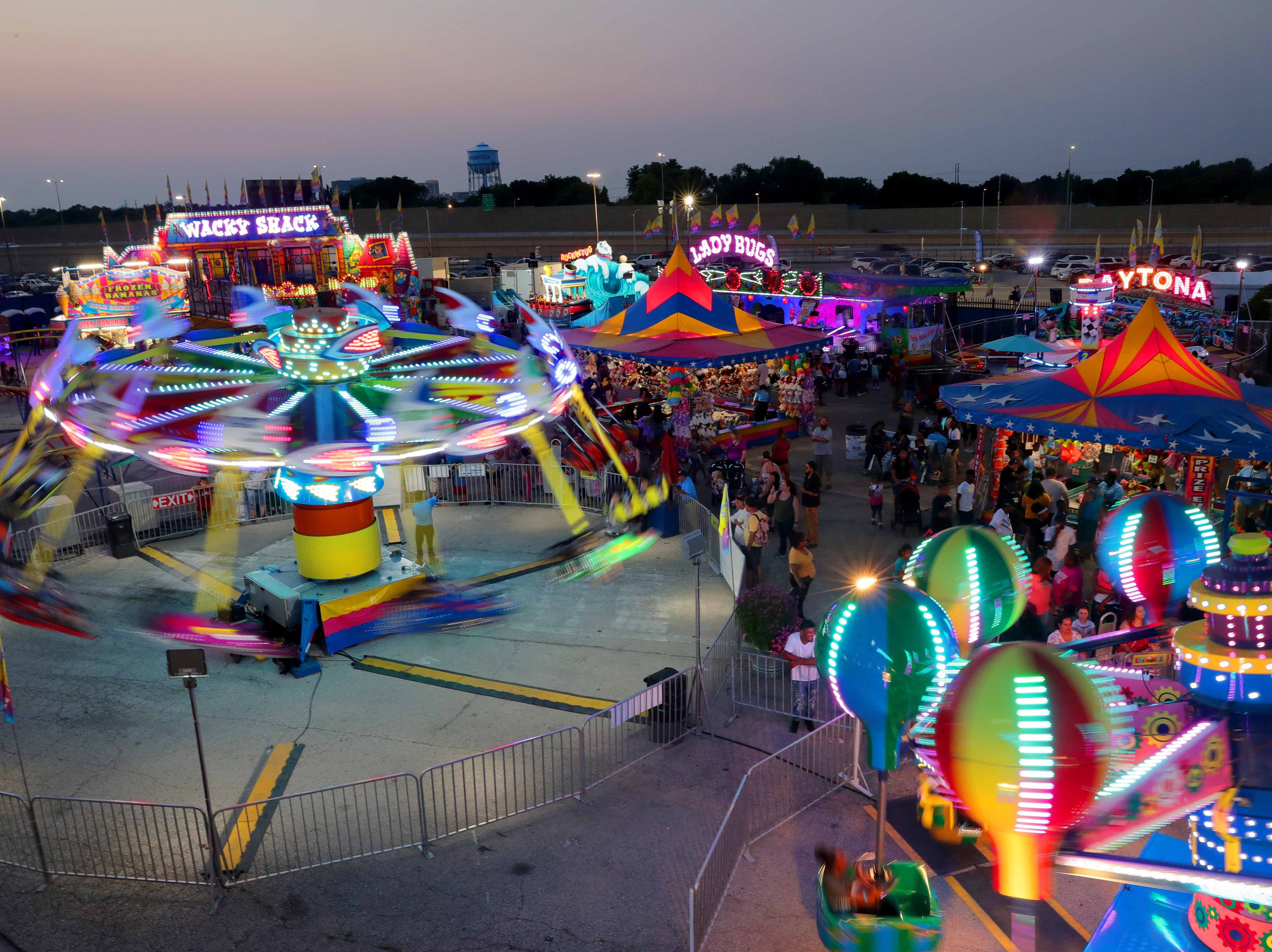 Fairgoers enjoy the rides in SpinCity on the final night of the Wisconsin State Fair Sunday, Aug. 12, 2018.