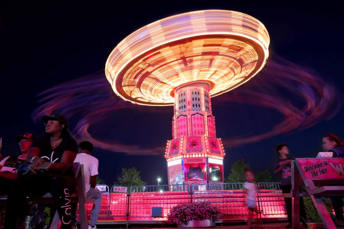 Fairgoers enjoy the swing ride in SpinCity on the final night of the Wisconsin State Fair Sunday, Aug. 12, 2018.
