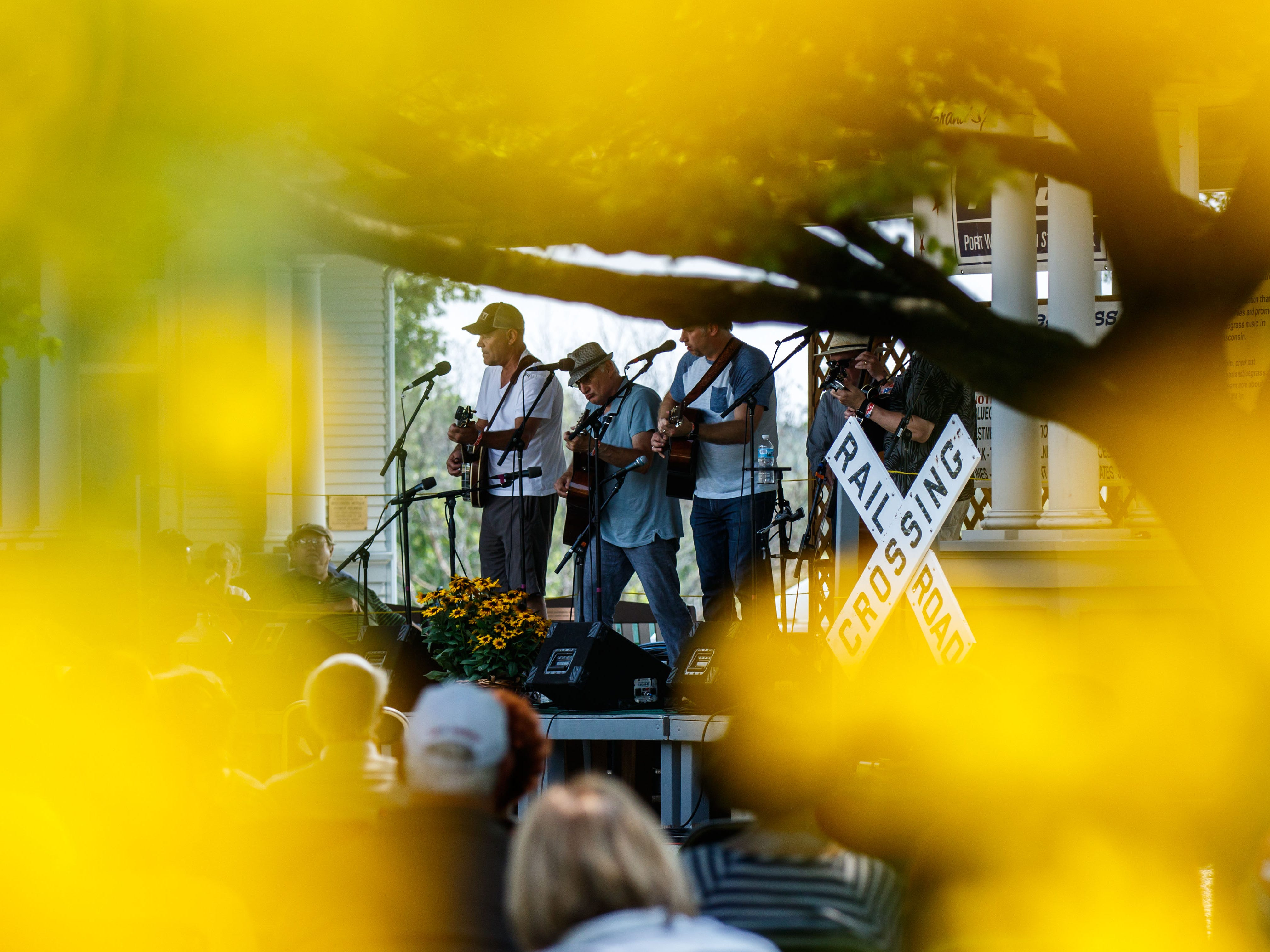 The band Sawdust Symphony is seen through colorful foliage at Ozaukee County Pioneer Village in Saukville during Bluegrass at the Village on Sunday, August 12, 2018. The annual event features live music, food and beverages, crafts, raffle items and more.