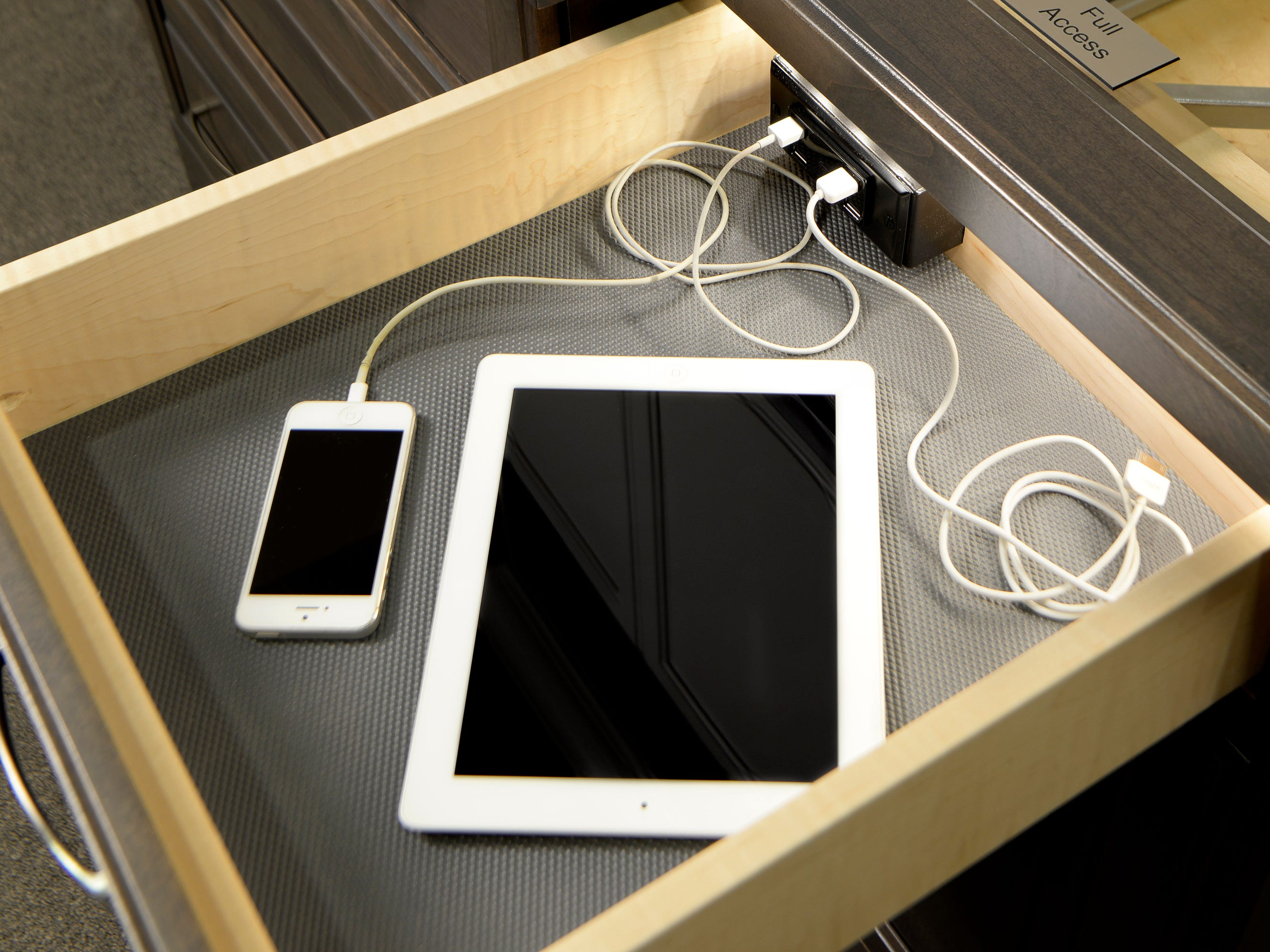 A pull-out drawer permits hidden charging of phones and tablets.