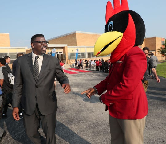 Audubon Tech Principal Leon Groce  wears the cardinal mascot's headgear while the student mascot went to get some water. Interim MPS Superintendent Keith Posley jokes with him.