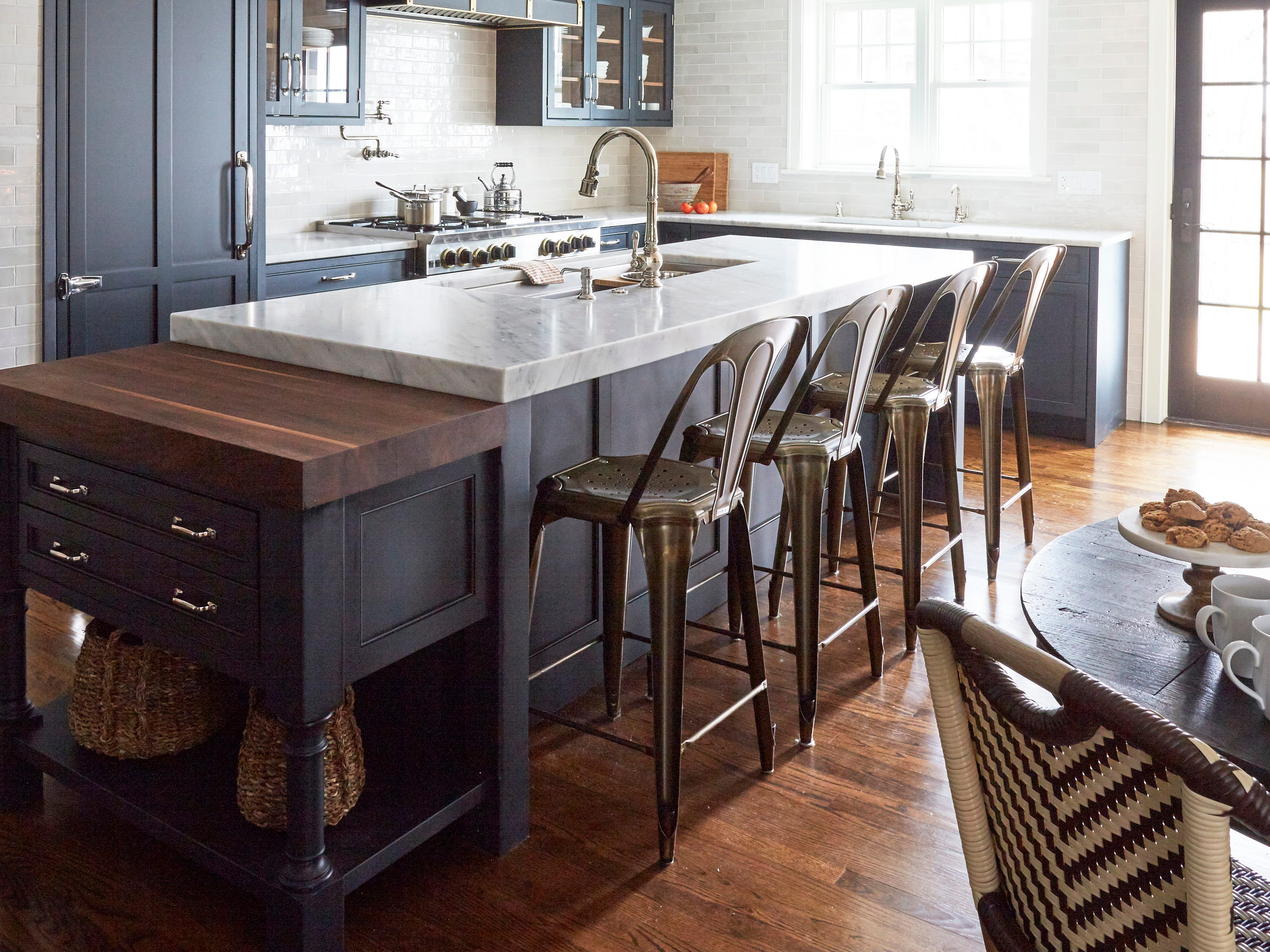 This multipurpose island for family of cooks is painted in BM Inkwell, with a galley sink and two faucets and a lower-level island in walnut for dedicated prep, with a cutting board.