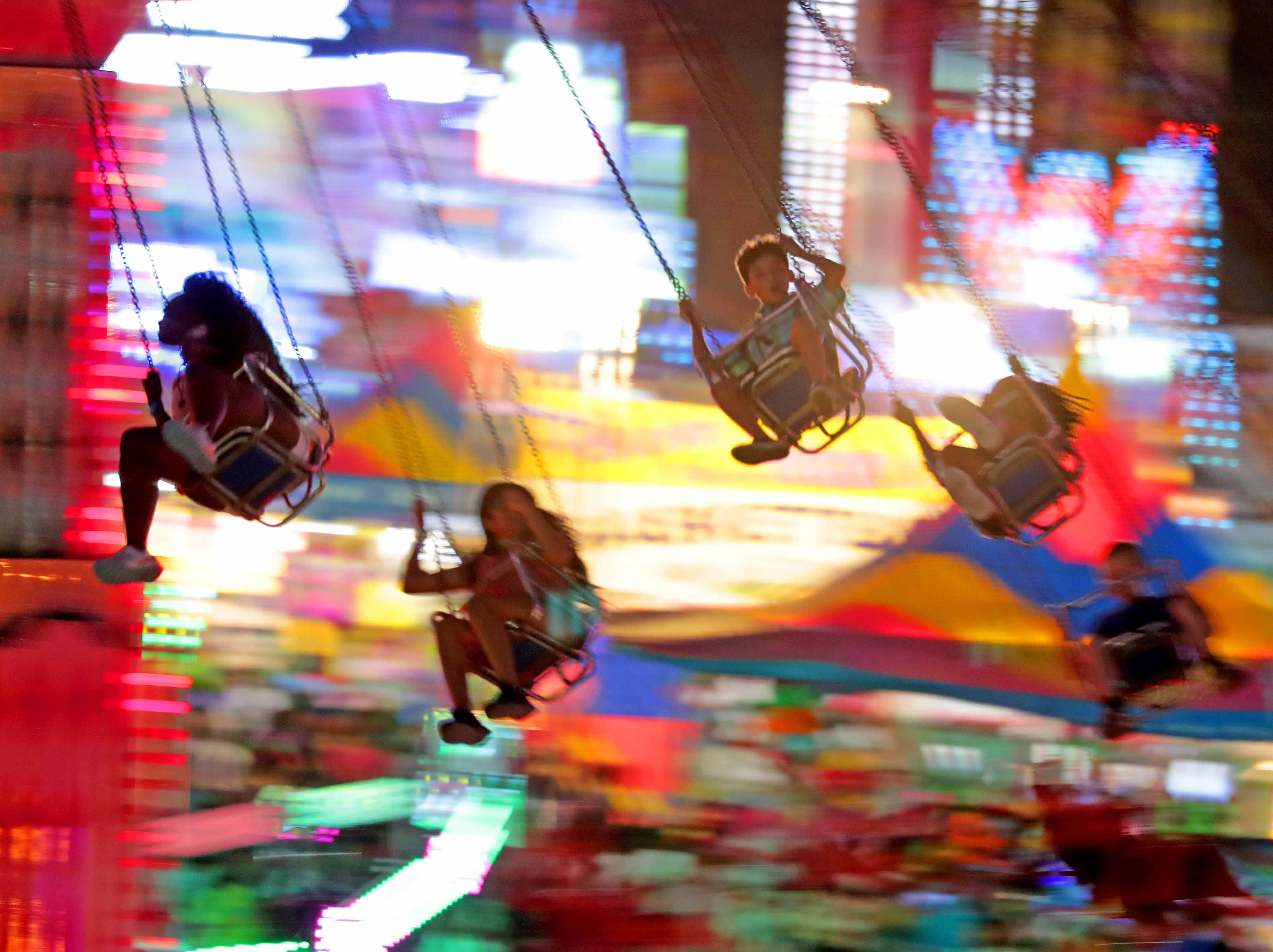 Fairgoers enjoy the swing ride in SpinCity at the Wisconsin State Fair.