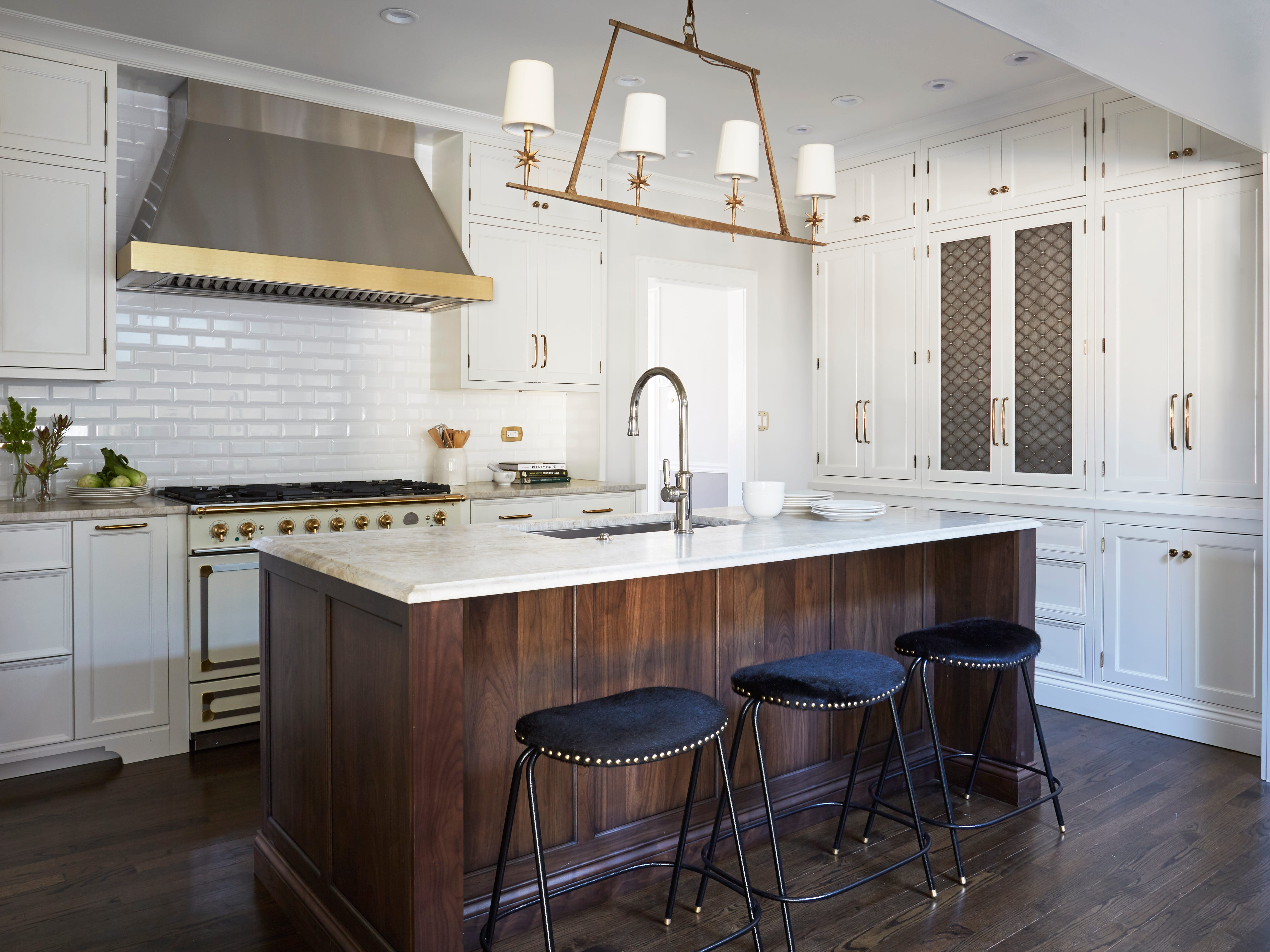 This walnut island has a quartzite countertop with Ogee edge; it contrasts well with the brass accents in this kitchen.