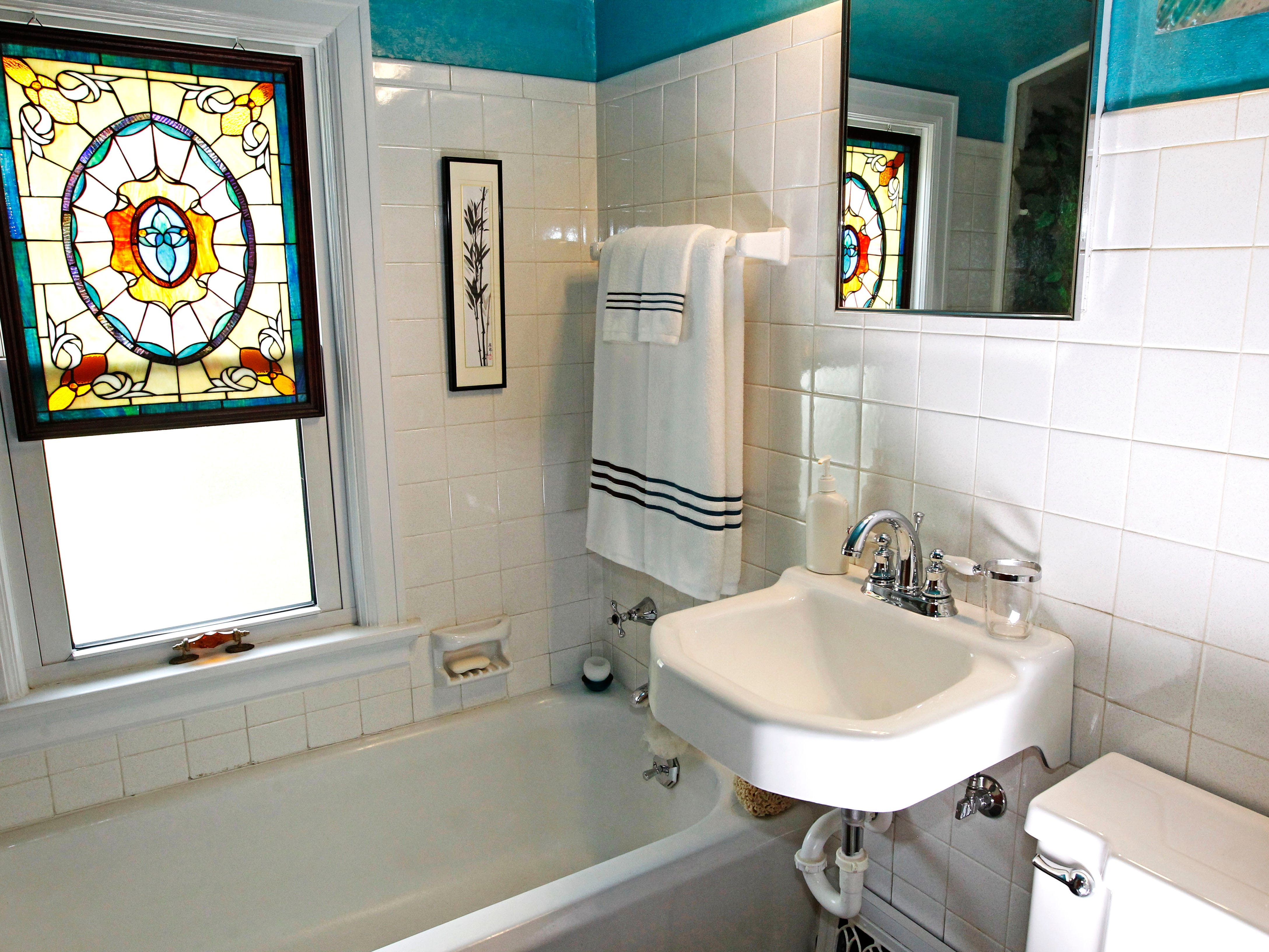 The upstairs bathroom is done in bright aqua blue with white  tile walls.