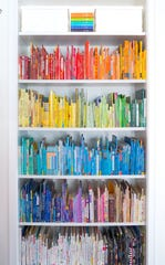 A bookshelf organized by The Home Edit, demonstrating their ROYGBIV color style.