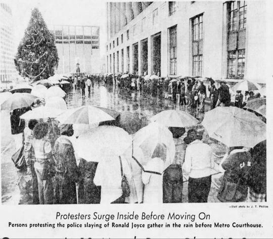 "The caption of this Nov. 27, 1973, photo reads: ""Protesters surge inside before moving on. Persons protesting the police slaying of Ronald Joyce gather in the rain before Metro Courthouse."""
