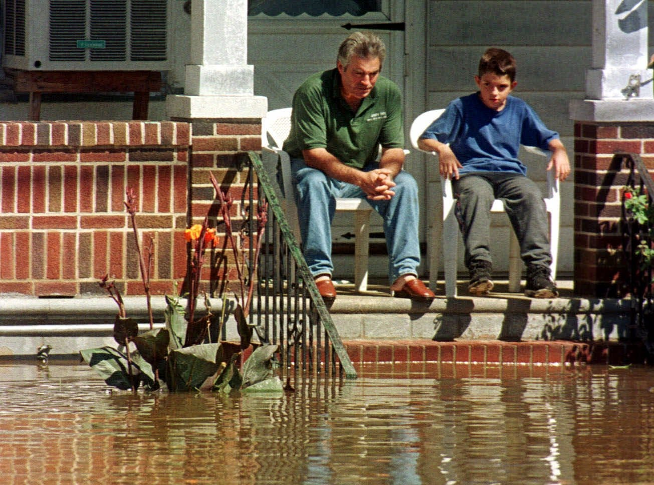 Sept. 17, 1999: A man and boy sit on their front porch surrounded by water and a  submerged car in their front yard in Lodi. Lodi is one of the towns around the state that was inundated by flood waters from Hurricane Floyd.