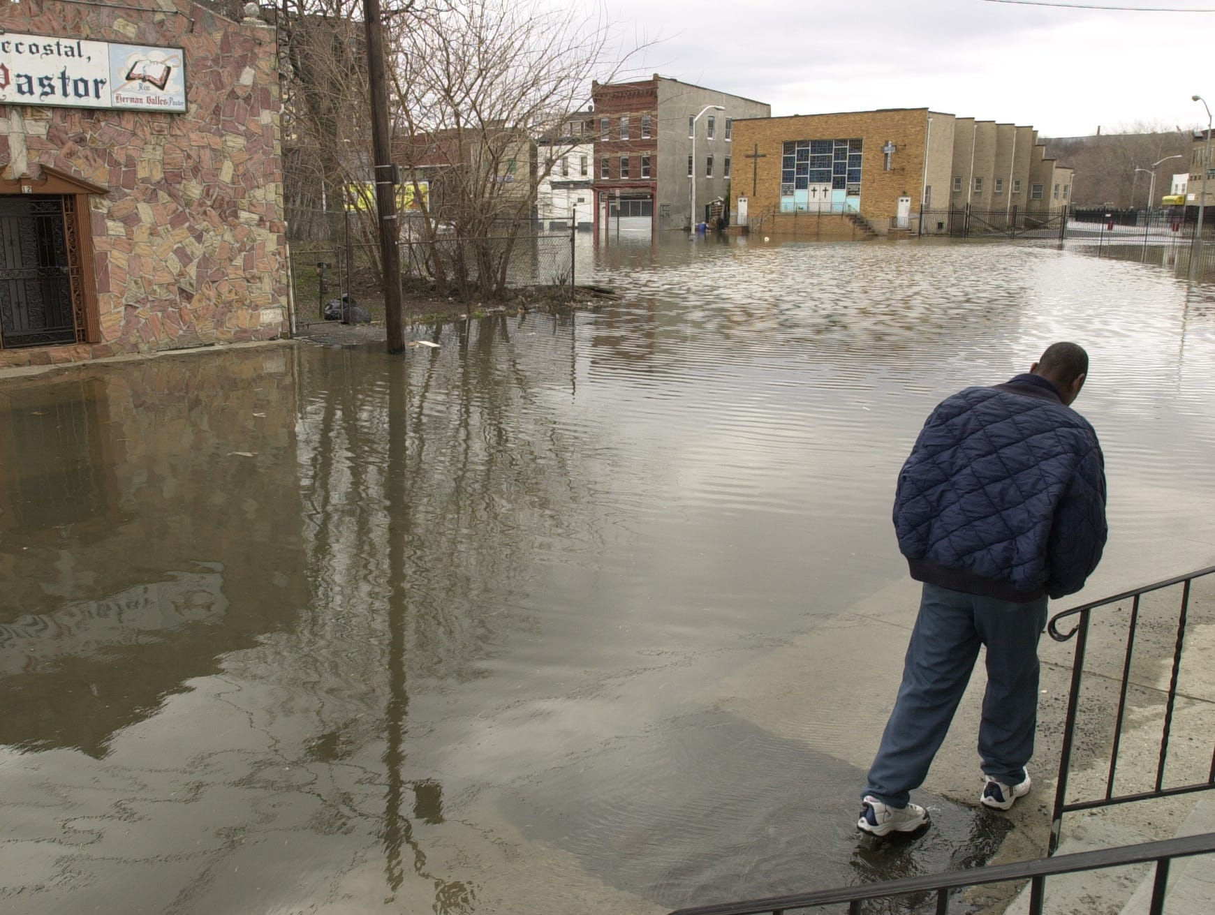April 4, 2005: Flooding in Paterson near Passaic River and Bridge Street.  Reginald Warner surveying flood conditions on Governor St. near Bridge Street as the water continued to rise Monday morning.  He said it was the worse flooding since Hurricane Floyd.