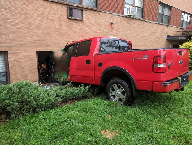 A pickup truck rammed into the side of a building after a three-car accident.