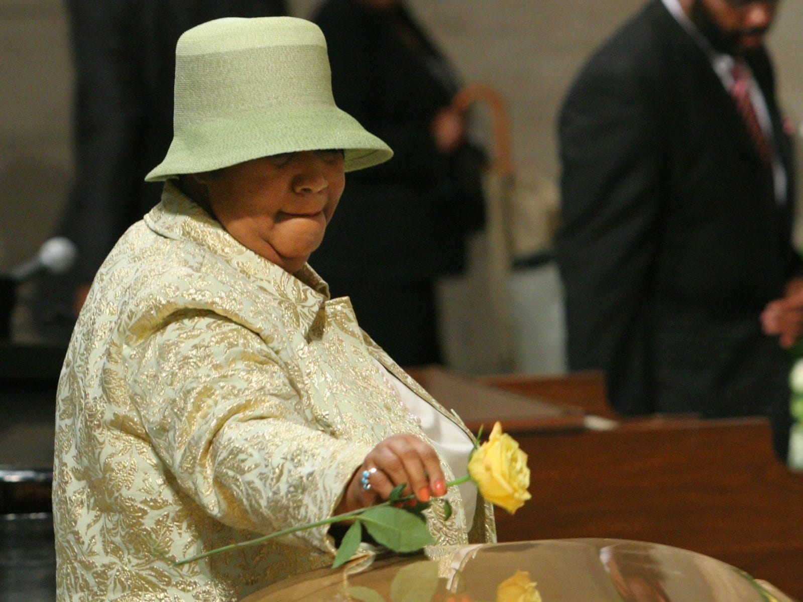 Aretha Franklin place a rose on the casket of Luther Vandross before she sings at his funeral, Friday July 8, 2005 in New York.