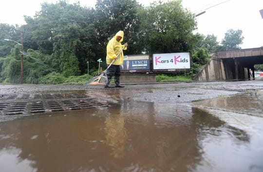 Frank Orrico, of Sterling Group Management, cleared debris from flood water at the intersection of Elm Ave. and River Rd. in Bogota.  A bride had to be rescued from flood waters here this past weekend. Monday, August 12, 2018