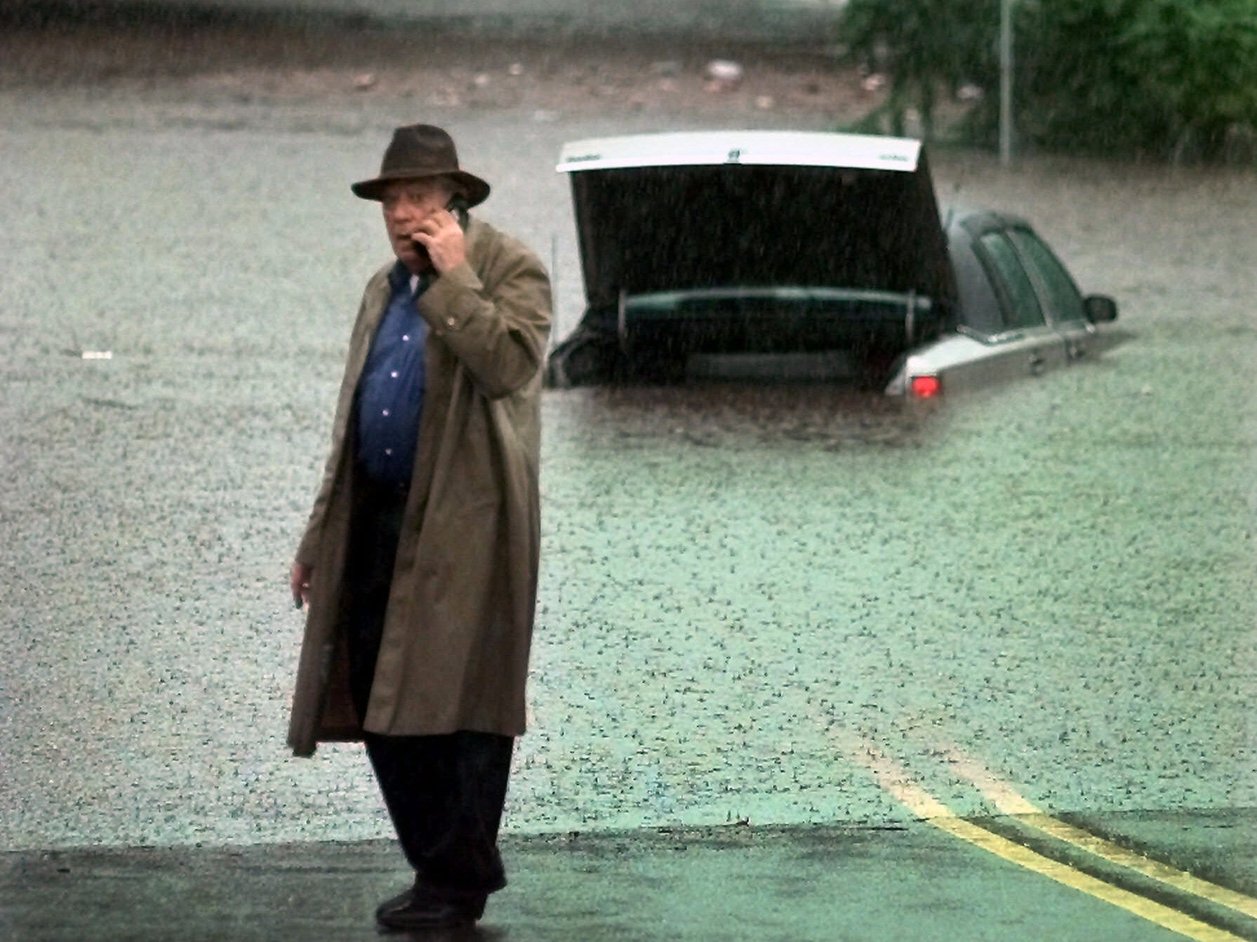 Sept. 16, 1999: A man, who would not give his name, calls for help on a cellular phone after he drove his car into deep flood waters in Newark. The outer bands of Hurricane Floyd began to sweep through New Jersey Thursday bringing heavy rain and gusty winds.