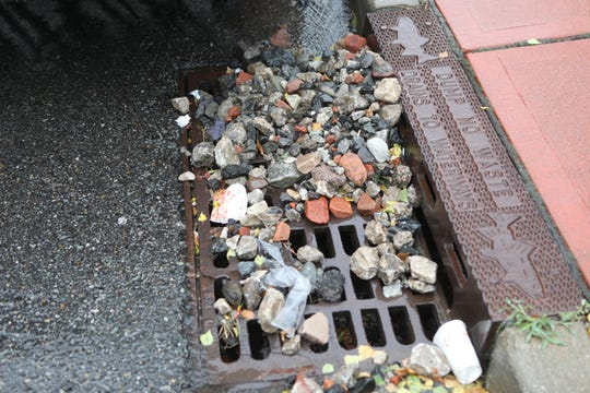Four days after flood waters sent rocks down a Fairview cliff to Fairview Gardens rocks can still be seen in the area including this sewer on Prospect Ave. Monday, August 12, 2018