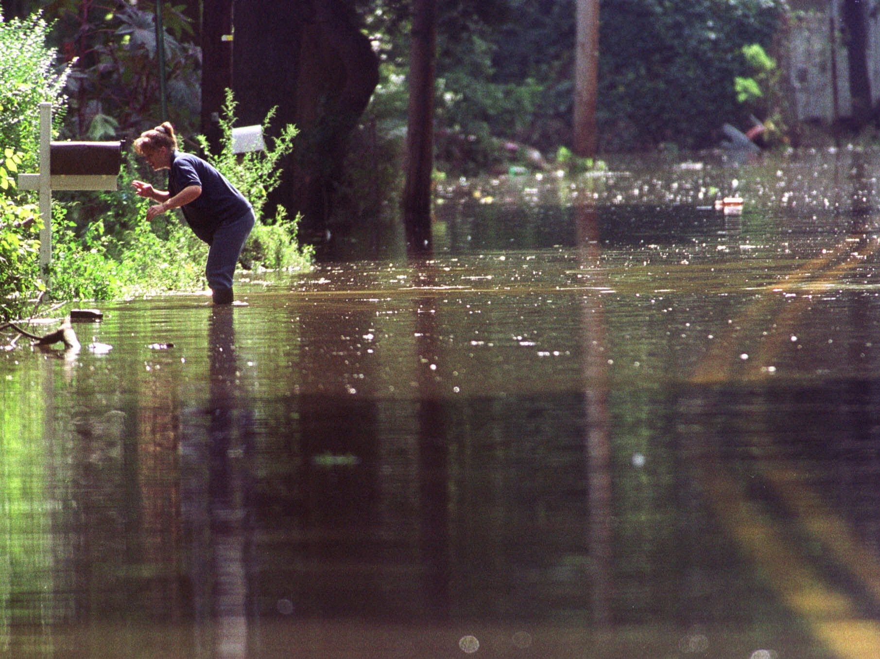 Sept. 19, 1999: A resident checks her mailbox on a still-flooded street in the Mt. View section of Wayne. On the fourth day after Hurricane Floyd drenched the state with record and near record rain falls, some rivers remained above their flood stage.