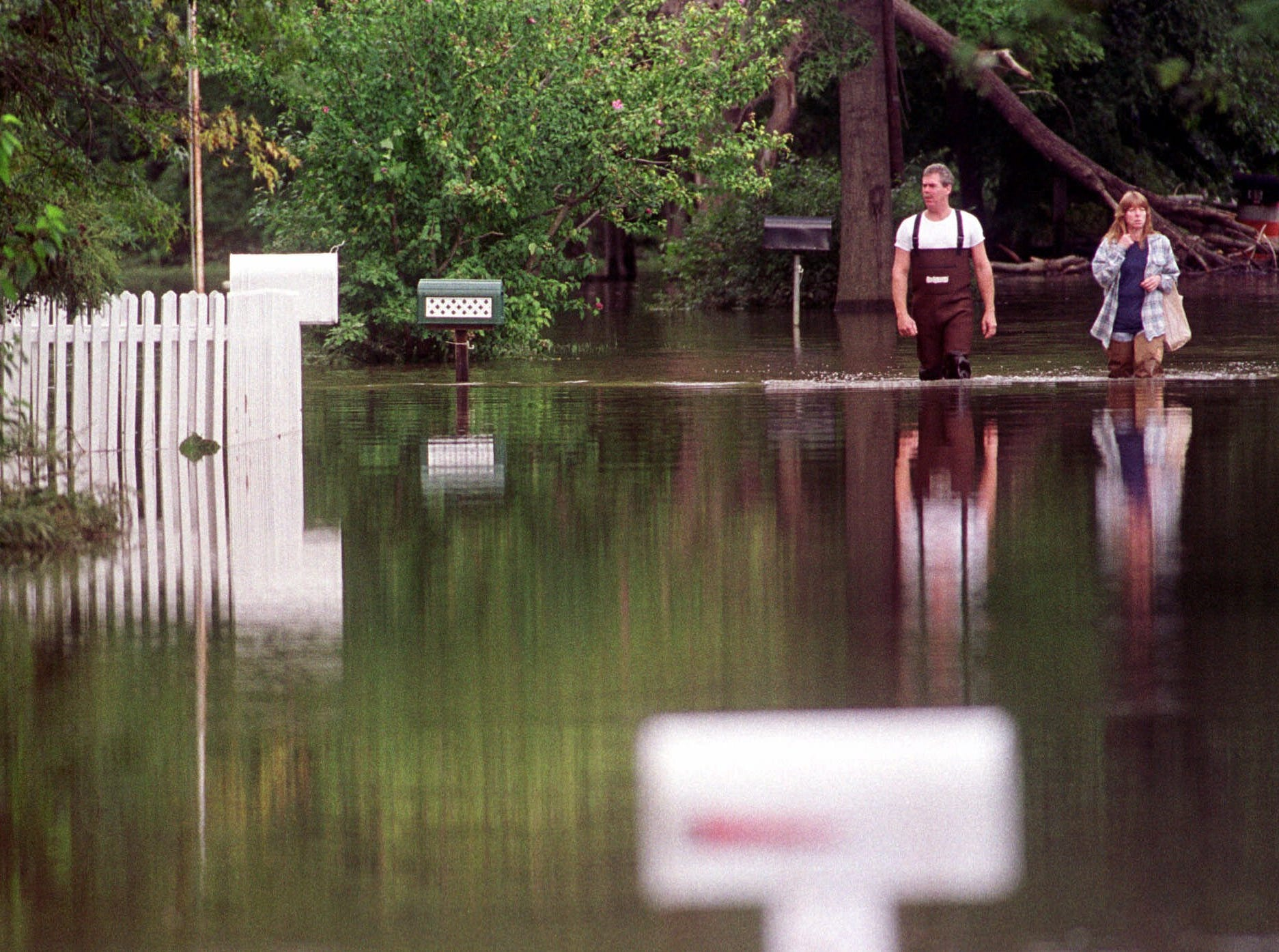 Sept. 19, 1999: Peter Jackson and his wife, Nancy, walk down their still-flooded street in Wayne. The Jackson's, who have lived here for 20 years, say their house was spared the flood caused by Hurricane Floyd because it is built up above flood height.