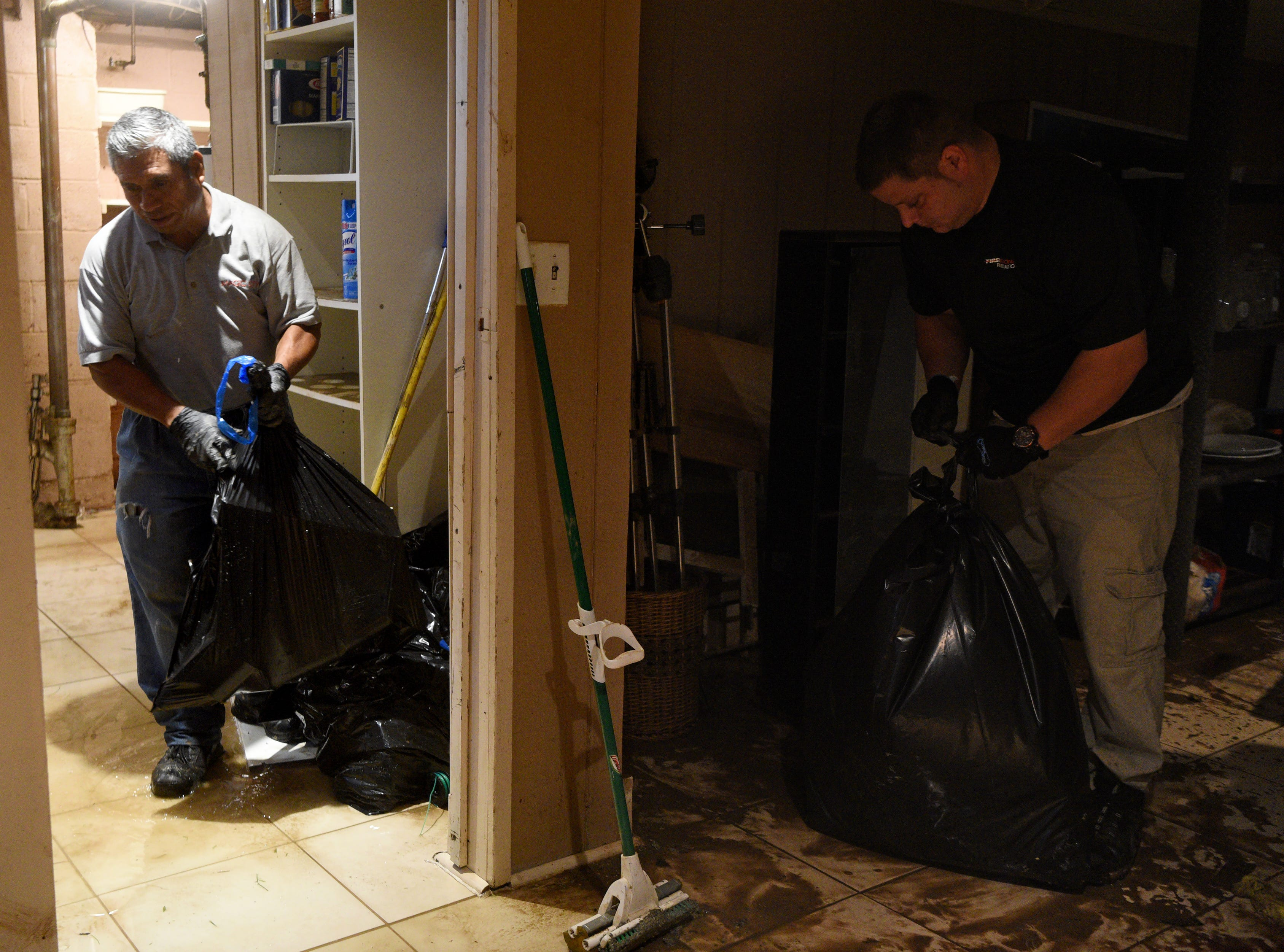 Employees of First Response Restoration hired by a resident on Ryle Ave. in Little Falls clear out the contents a flooded basement on Monday, August 13, 2018. Flooding in the area on Saturday caused the Peckman River to over flow causing some of the worst flooding in the area since Hurricane Floyd.