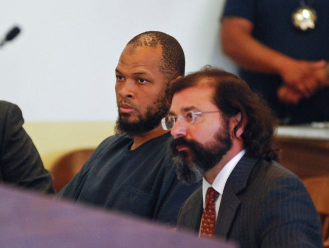 Siraj Ibn Wahhaj, left, sits next to public defense attorney Aleks Kostich at a first appearance in New Mexico state district court in Taos, N.M., Wednesday, Aug. 8, 2018, on accusations of child abuse and abducting his son from the boy's mother. Authorities were waiting to learn if human remains found at a disheveled living compound were those of Wahhaj's missing son. Authorities also allege Wahhaj was conducting weapons training with assault rifles at the compound near the Colorado border where they say they found 11 hungry children living in filthy conditions in a raid Friday.