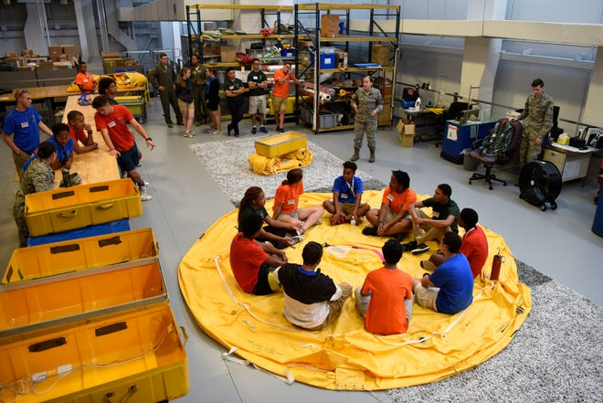 Students of the Aviation Character and Education Flight Program sit inside a life raft during their tour of Aircrew Flight Equipment July 19, 2018, at Dover Air Force Base, Del. The life rafts are able to hold 25 people and are a mandatory item aboard mobility aircraft.