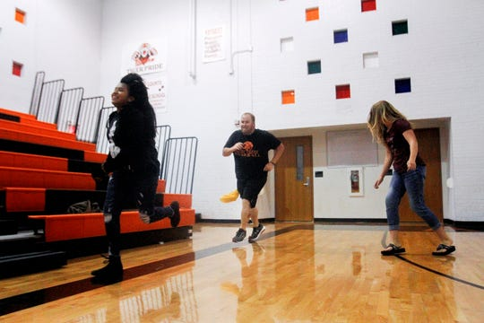 C.V. Koogler Middle School Physical Education teacher Paul Mitchell, center, plays tag with his students during an activity Monday at C.V. Koogler Middle School in Aztec.