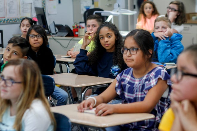 Students listen to social studies teacher Gary Zuniga Monday during the first day of classes at C.V. Koogler Middle School in Aztec.