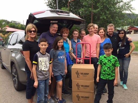 Volunteers help Emmet Fallon, cattle rancher in Fort Sumner, unload his generous donation of beef to the Lincoln County Food Bank.