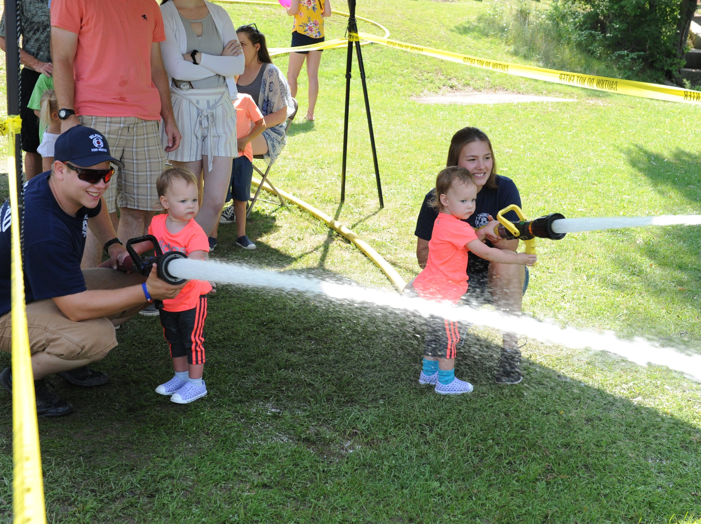 Milford Firefighter John Siekierka, twin sisters, Cecilia and Renee Dreslinski and Cadet McKenzie Chappell work the fire hoses at Milford Memories.