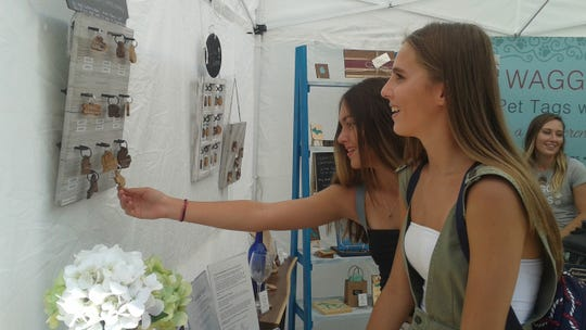 """Maya Goudeseune (foreground) of Wolverine Lake, and Jaden Frigerio of Commerce Township, check out the  pet tag selection at the Waggz Tags booth during Milford Memories.  Goudeseune called the handcrafted tags """"aesthetically pleasing."""""""